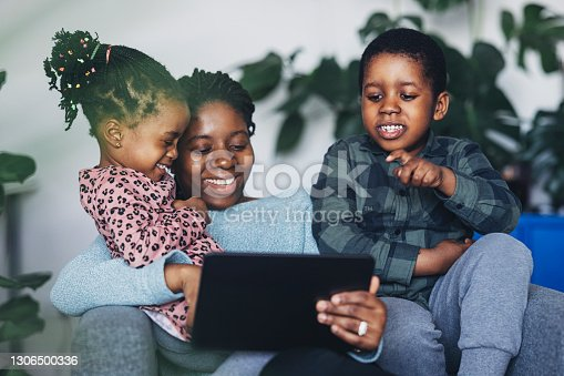 A portrait of a beautiful happy young African-American mother and her young boy and a girl using a digital tablet while spending creative time together at home.