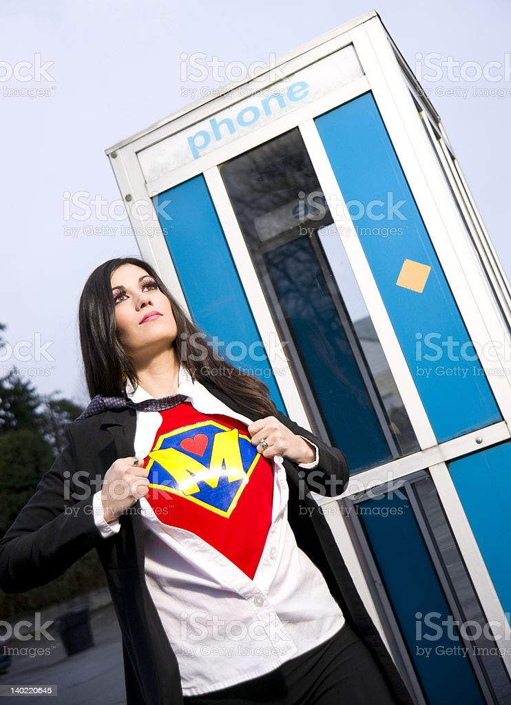 Super Mom Hero Emerges from Phone Booth Tearing Clothes off stock photo