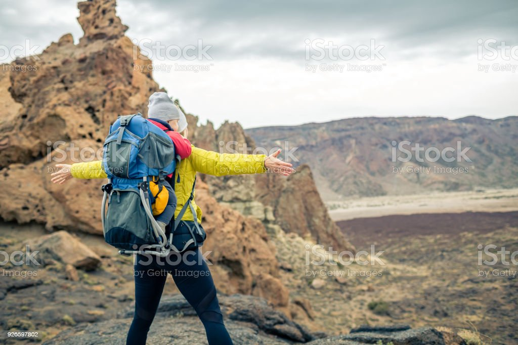 Super mom with baby boy hiking in backpack stock photo