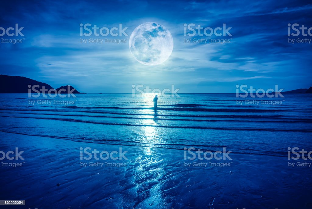Super moon. Colorful blue sky with bright full moon over seascape and...
