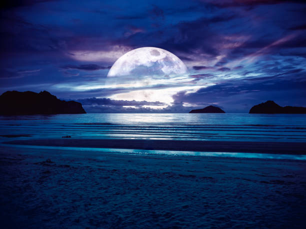 Super moon. Colorful sky with bright full moon over seascape. Serenity nature background, outdoor at gloaming. stock photo