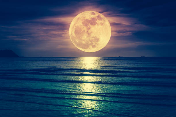super moon. colorful sky with cloud and bright full moon over seascape. - romantic moon stock photos and pictures