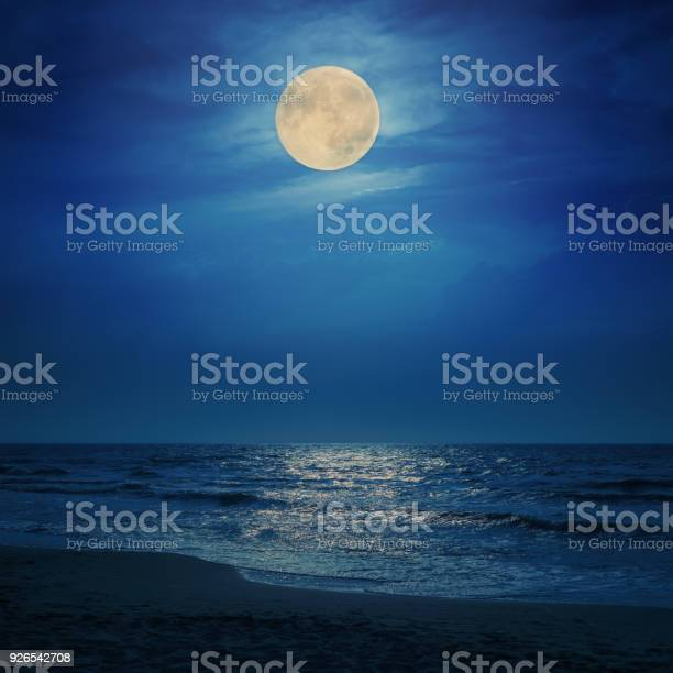 Photo of super moon in clouds over sea