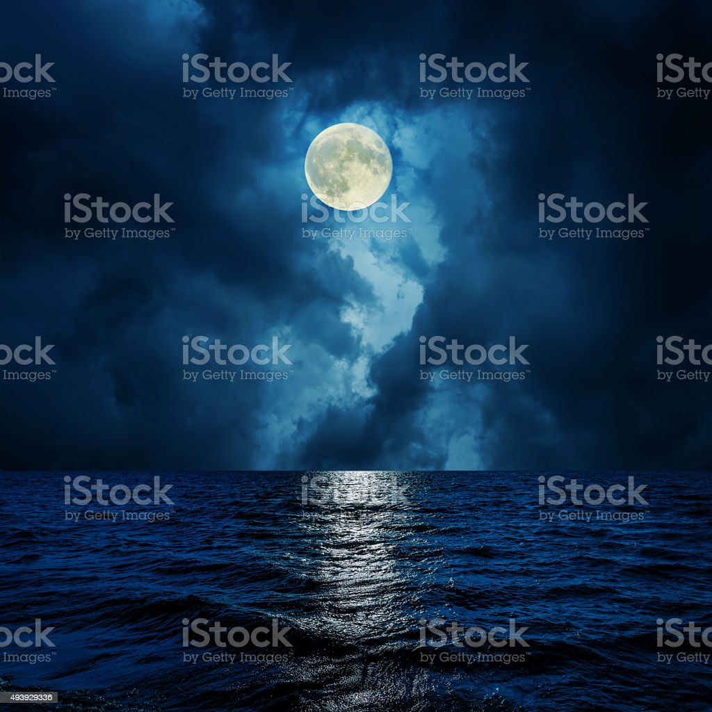 super moon in clouds over water stock photo