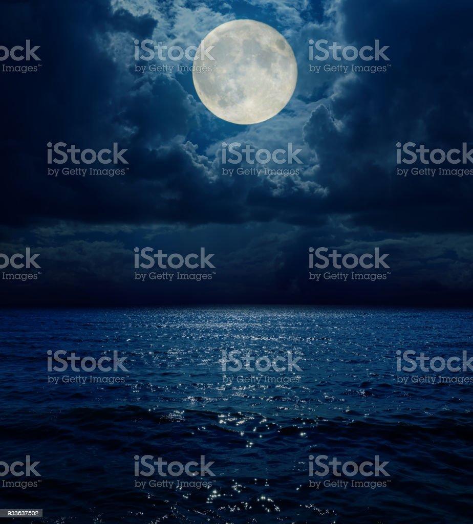 super moon in dark clouds over sea stock photo