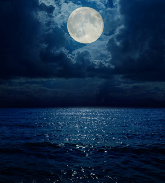 super moon in dark clouds over sea - moon stock pictures, royalty-free photos & images