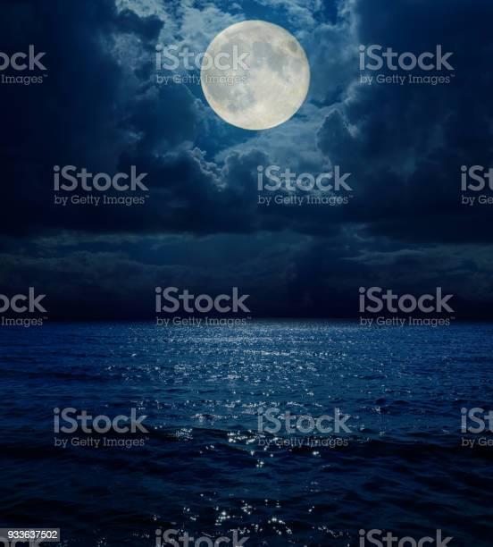 Photo of super moon in dark clouds over sea