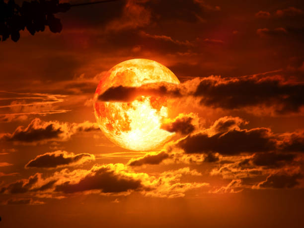 super moon on silhouette cloud in red sky stock photo