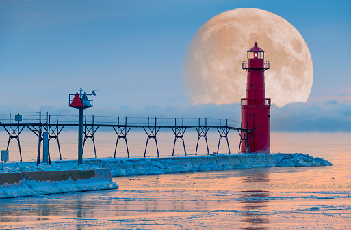 Super moon rises out of steaming Lake Michigan waters, behind majestic lighthouse, in subzero Winter cold.