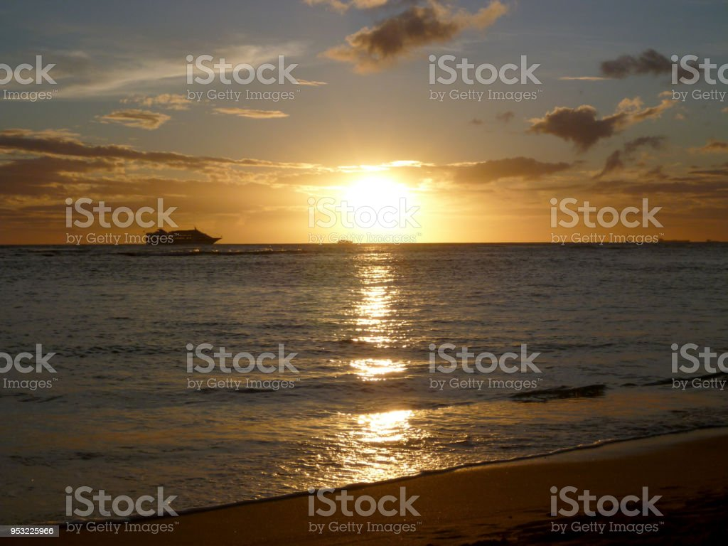 Super Sunset though the clouds and reflecting on the Pacific ocean stock photo