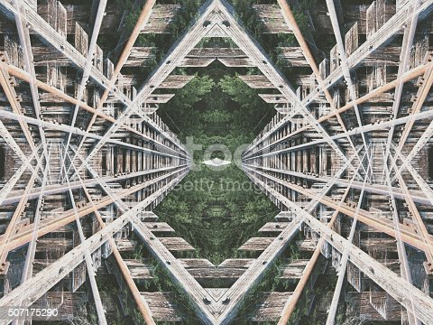 The criss-crossing confusion of a mirrored abandoned railroad bridge.  Composite image.
