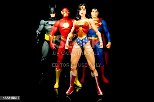 Vancouver, Canada - October 9, 2012: Action figure models of Wonder Woman, The Flash, Superman and Batman, released by DC comics, against a black background.