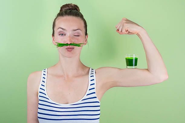 Super wheat grass power! Fit and strong with wheat grass juice chlorophyll stock pictures, royalty-free photos & images