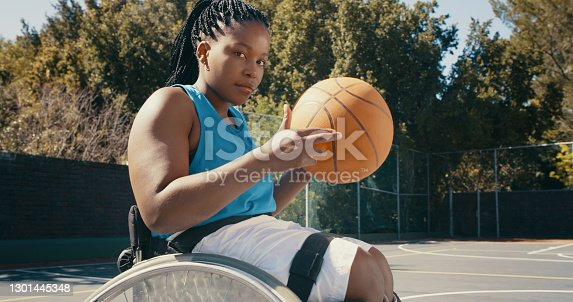 Shot of a young female wheelchair basketball player looking at the camera while holding the ball
