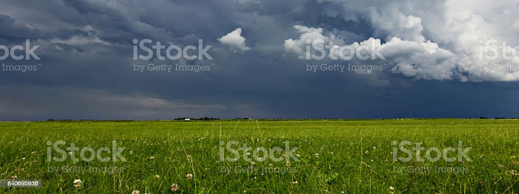 Supercell storm clouds above meadow with green grass Summer Storm...