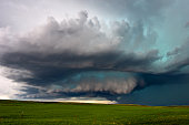 Supercell thunderstorm with dramatic, dark clouds over a scenic Montana landscape.