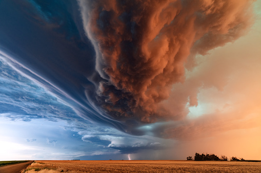 Supercell thunderstorm with dramatic storm clouds at sunset during a severe weather outbreak in Kansas.