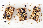 Superfood breakfast bars, above view on marble background
