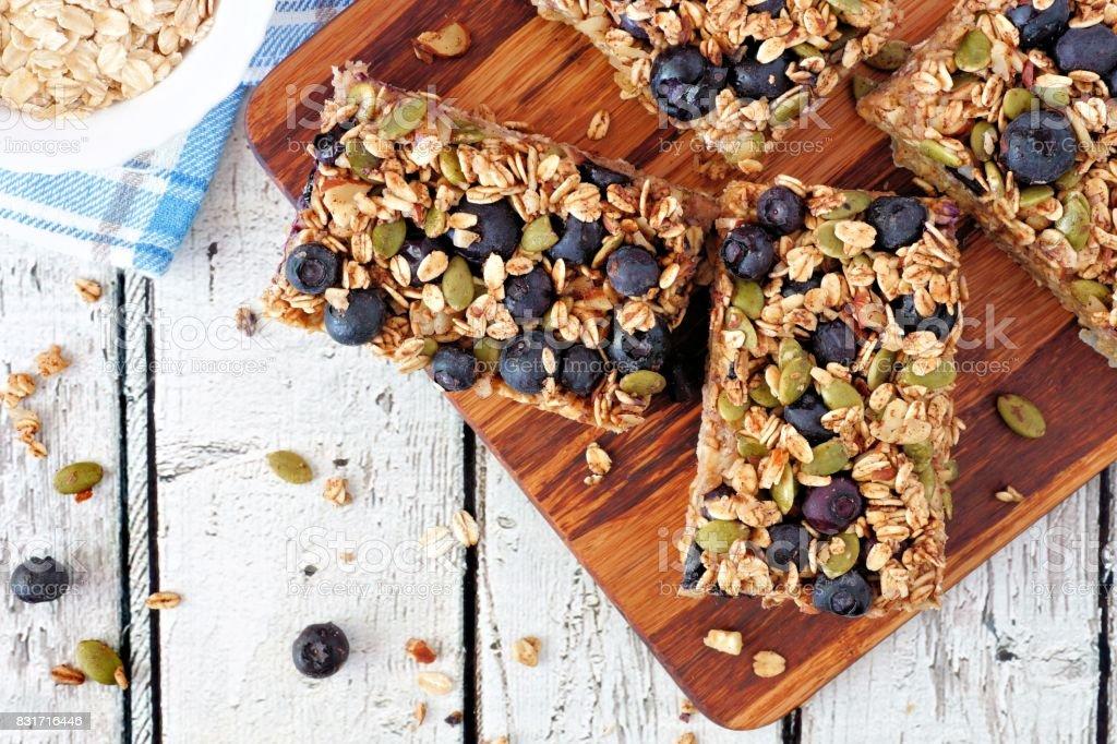 Barras de pequeno-almoço superalimento com aveia e mirtilos na placa de madeira - foto de acervo