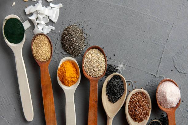 superfood in löffel über grauen beton hintergrund - quinoa superfood stock-fotos und bilder