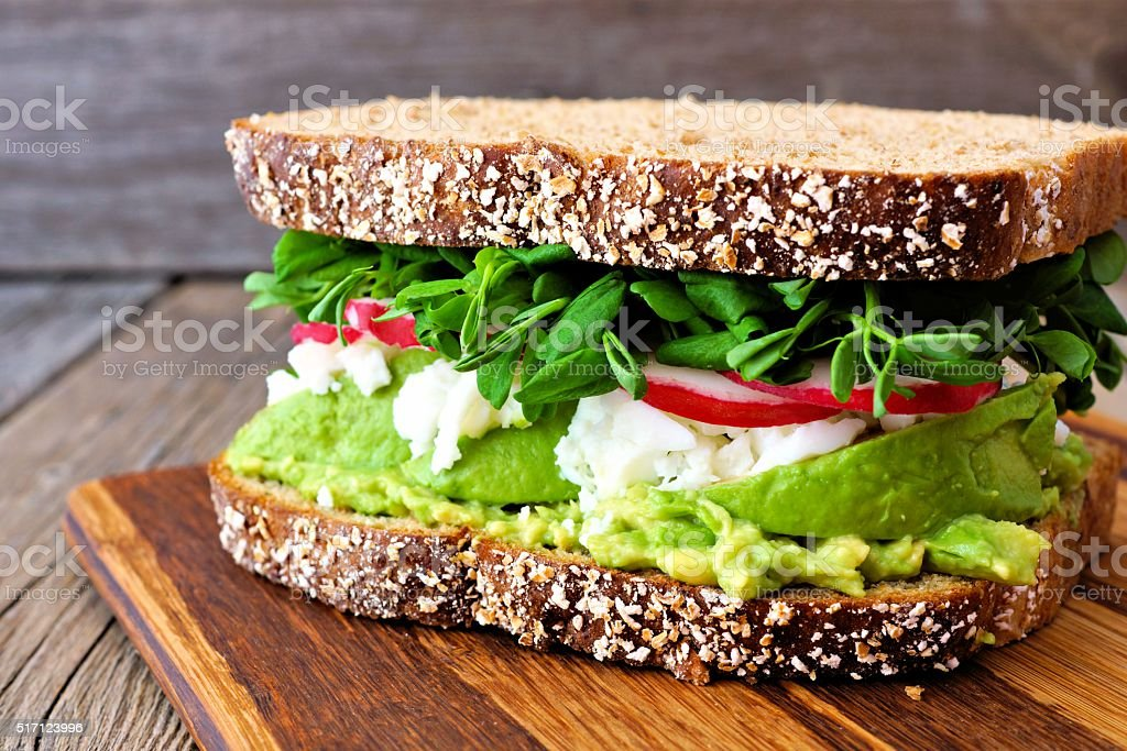 Superfood sandwich with, avocado, egg whites, radishes and pea shoots stock photo