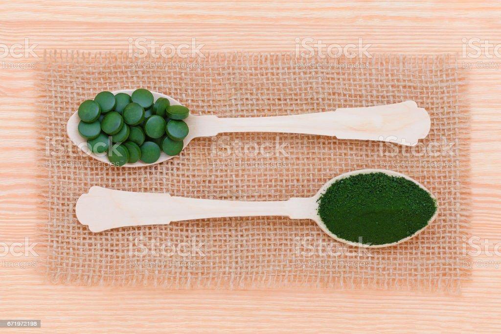 súper alimento, algas, pastillas de espirulina y Clorella y el polvo en cucharas de madera con marco, estilo de vida saludable - foto de stock