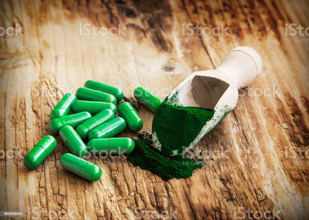Superfood spirulina powder and pills on wooden background stock photo