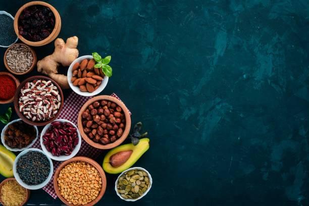 Alimentação saudável superalimentos. Porcas, bagas, frutas e legumes. Sobre um fundo preto e pedra. Vista superior. Espaço de cópia gratuita. - foto de acervo