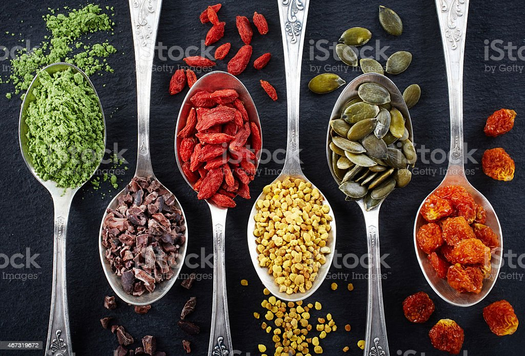 Superfoods in separate spoons laid next to each other stock photo