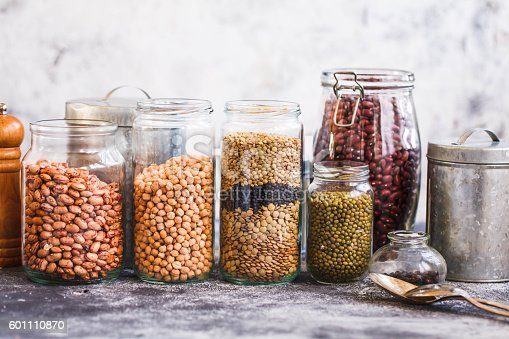 Collection of grain products, lentils, peas, soybeans and red beans in storage jars over on kitchen rural table. Vegetarian products.