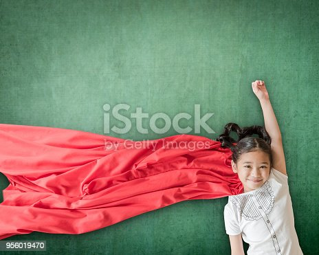 istock Superhero Asian school girl kid student with inspiration in women rights in education success concept 956019470