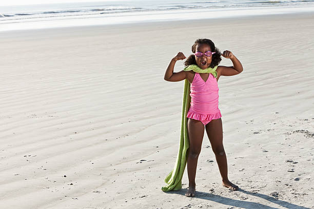 superhero at the beach - girl alone in swimsuit stock photos and pictures