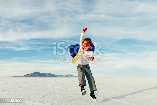 A young boy businessman is dressed up as a superhero with cape and jumps and flies through the sky while on the Bonneville Salt Flats in Utah, USA. This young entrepreneur is ready to take on challenges and lead his business into profitability.