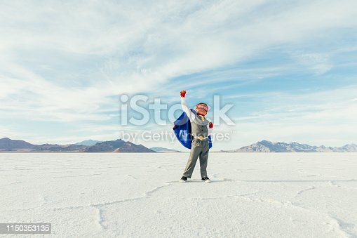A young boy businessman is dressed up as a superhero with cape and mask raises his arm in victory while on the Bonneville Salt Flats in Utah, USA. This young entrepreneur is ready to take on challenges and lead his business into profitability.