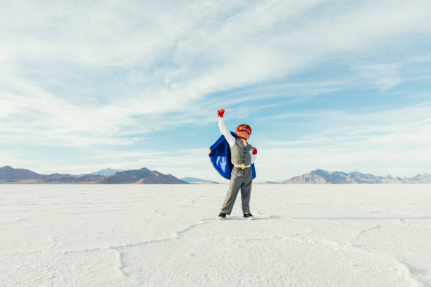 Superhero Business Kid with Arm Raised A young boy businessman is dressed up as a superhero with cape and mask raises his arm in victory while on the Bonneville Salt Flats in Utah, USA. This young entrepreneur is ready to take on challenges and lead his business into profitability. bonneville salt flats stock pictures, royalty-free photos & images