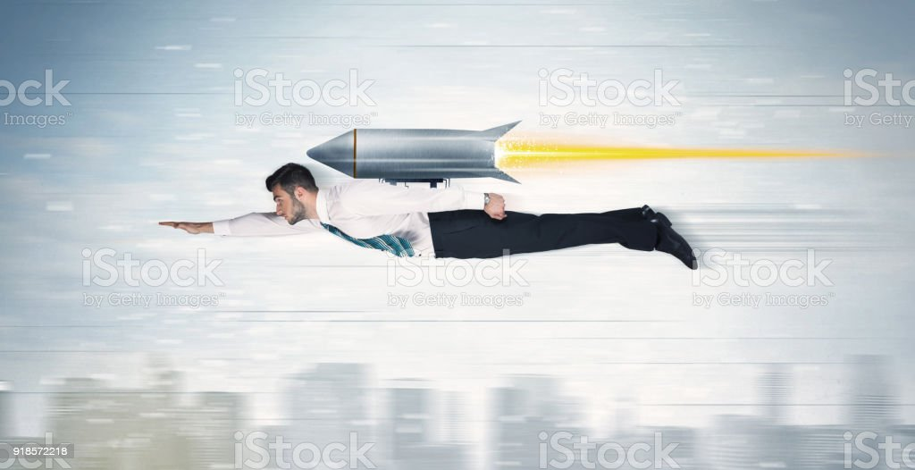 Superhero business man flying with jet pack rocket above the city stock photo