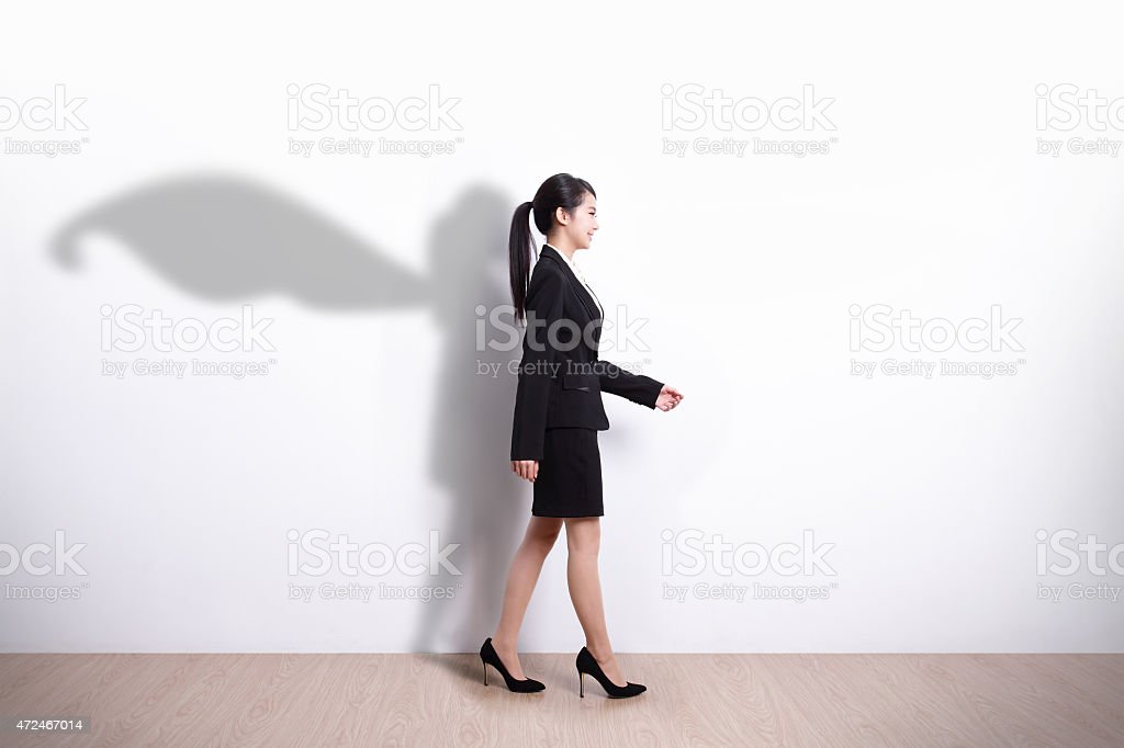 Superhero business woman walking stock photo