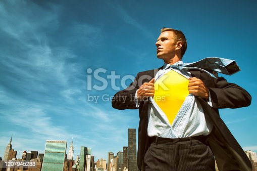 Strong young businessman revealing his inner superhero above the city skyline in bright sunny blue sky