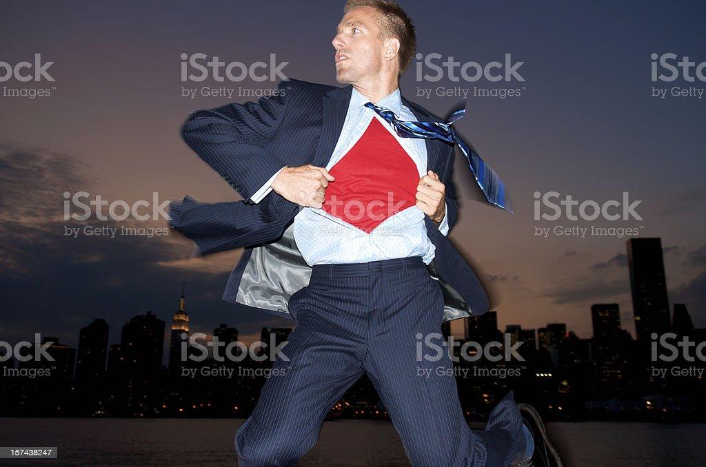 Superhero Businessman Flying Over Night City Skyline stock photo