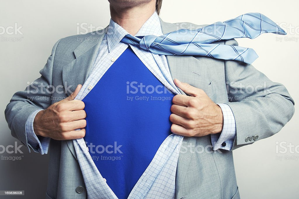 Superhero Businessman in Blue T-Shirt Pulling Suit Open stock photo