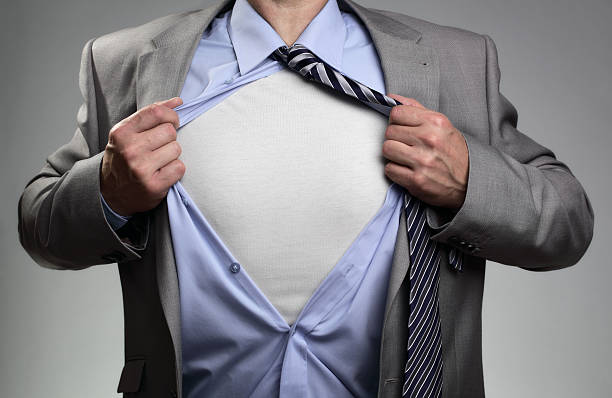 Superhero businessman Businessman in classic superman pose tearing his shirt open to reveal t shirt with blank chest for message fully unbuttoned stock pictures, royalty-free photos & images