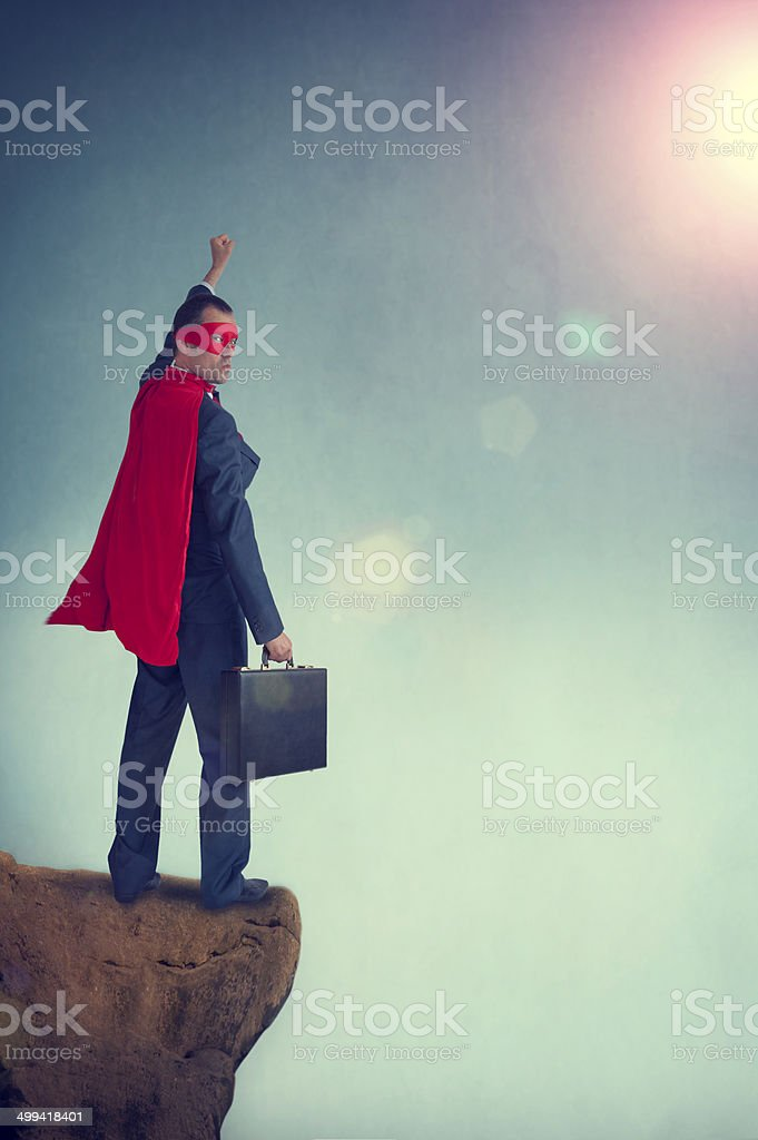 superhero businessman standing on the edge of a cliff stock photo