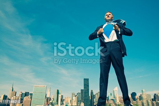 istock Superhero Businessman Standing Tall and Ready Above City Skyline 117148010