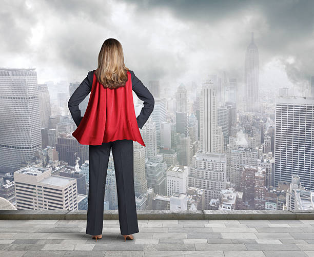 superheld geschäftsfrau mit red cape blick in die stadt - damen umhänge stock-fotos und bilder