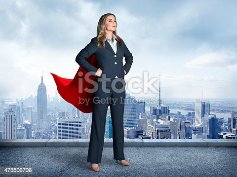 A businesswoman wearing a red cape strikes a super hero pose.  Her  hands on her hips and her feet are apart as she stands in front of the New York skyline.