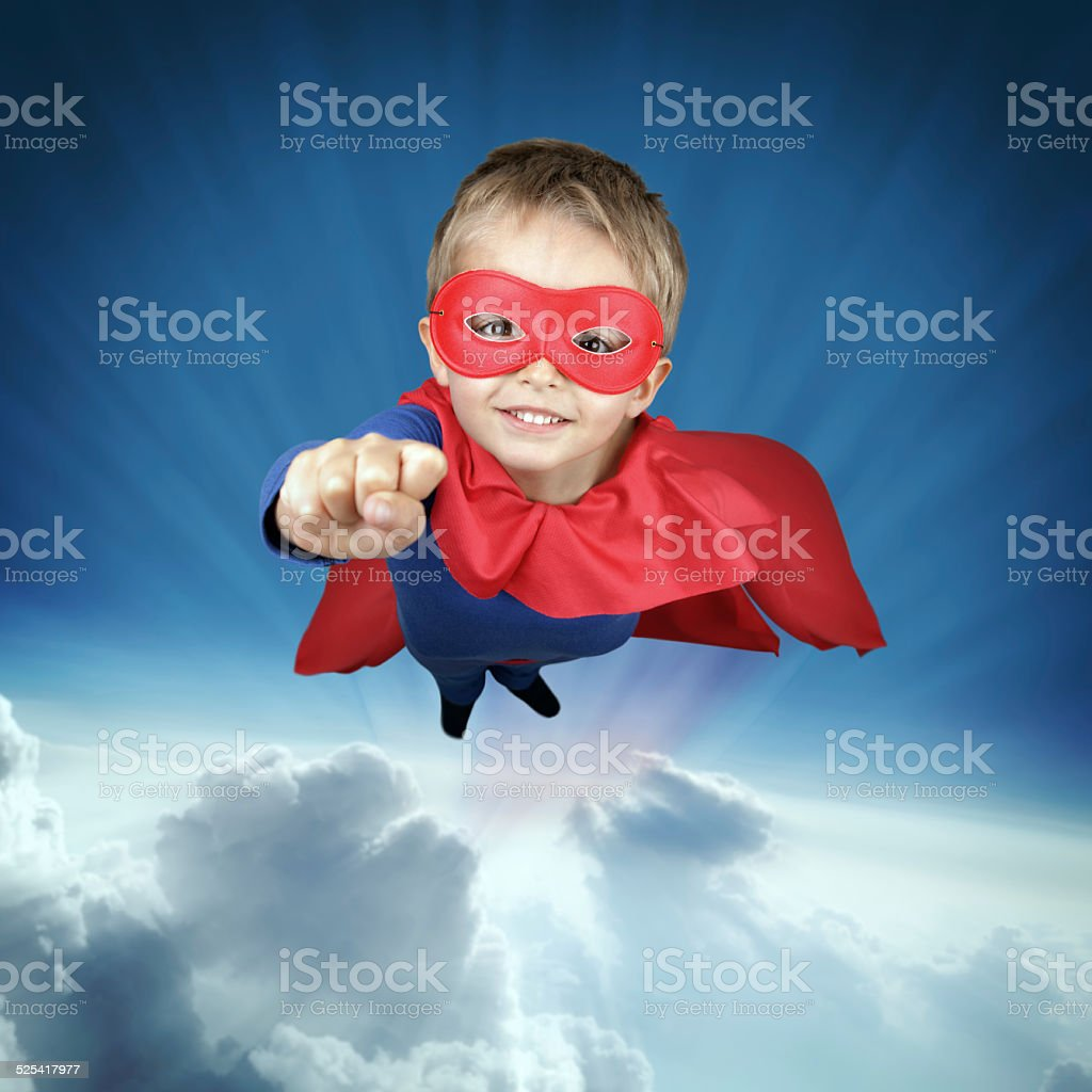 Superhero child flying above the clouds stock photo