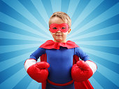 Superhero child with boxing gloves concept for childhood, imagination, aspirations and strength