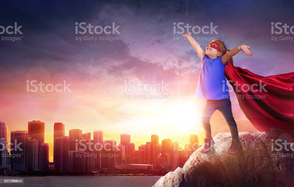 Superhero Child With Cityscape To Sunset stock photo