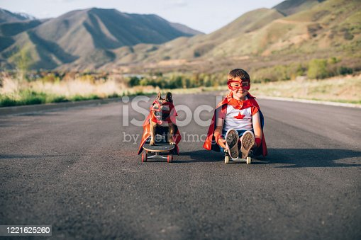 A young boy is dressed as a superhero is sitting on a skateboard along with his French Bulldog, who is also dressed as a super dog on a skateboard. They are the best of friends and are ready to conquer the enemy, namely cats and criminals. Image taken in Utah, USA.