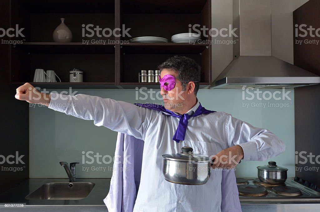 Superhero father cooking in home kitchen stock photo